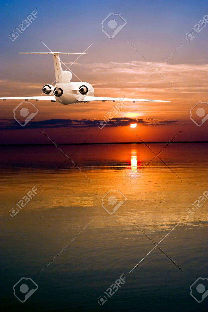 Commercial airliner fluing over water to sun Stock Photo - 3363443