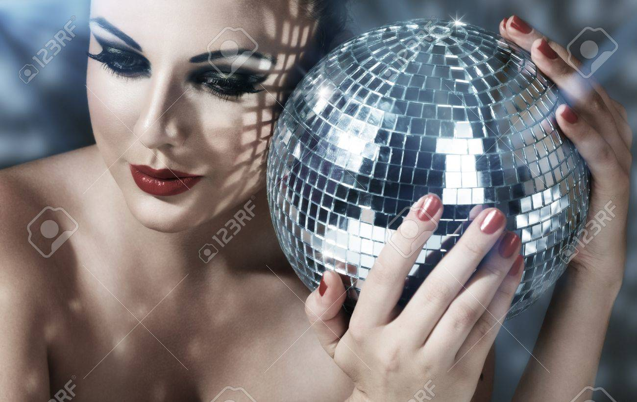 Close-up face of young woman with fashionable make-up and disco ball in hands Stock Photo - 12920829