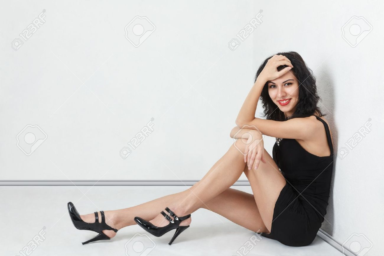 Attractive young slender woman with a long sexy legs sitting on floor in  empty room Stock