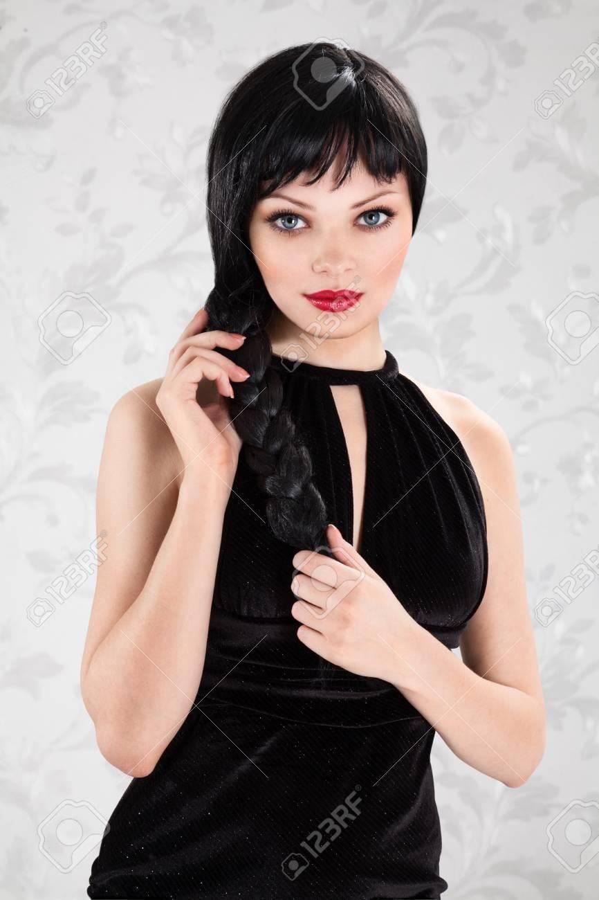 ビンテージ壁紙の背景の黒のドレスで美しい長い髪の若いセクシーな女性
