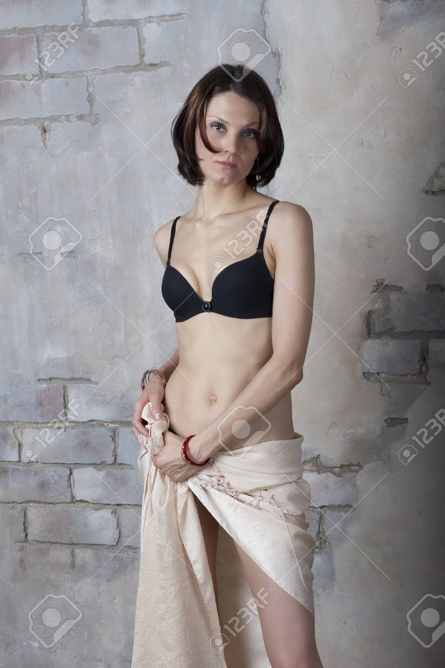 04bda23bde1 Young woman in black lingerie set against the old walls