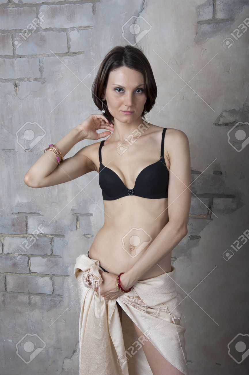 young woman in black lingerie set against the old walls stock photo
