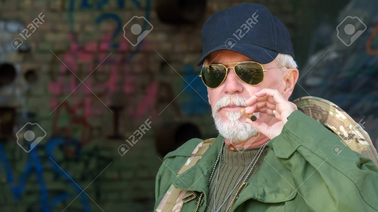 d1d5fb97da05a Portrait of confident elderly man wearing protective clothing in sunglasses  with a cigar against the background