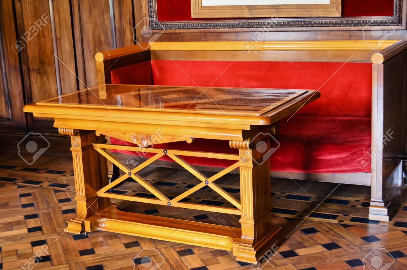 Antique table and a sofa with a red cloth Stock Photo - 24619042