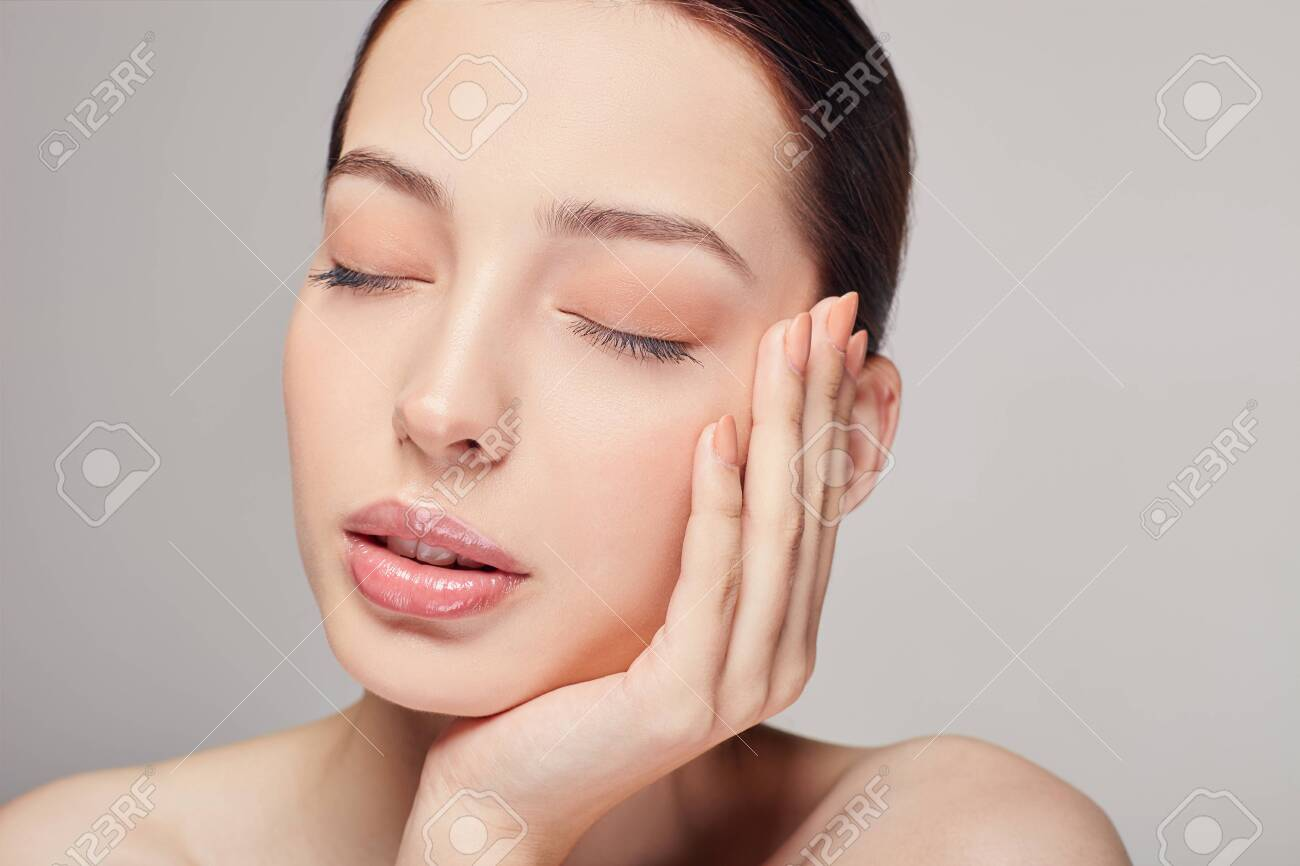 An elegant sophisticated beautiful girl with full lips, brown hair and clean delicate skin on the gray background. Lady put her head on her hand. Close eyes. Spa, face skin care. Wellness. - 134478597