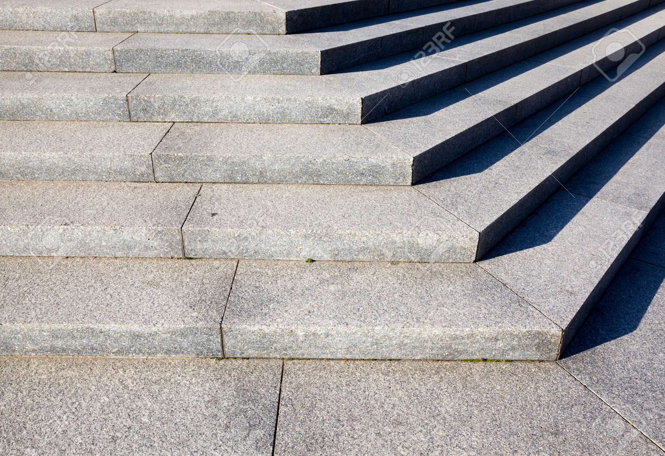 an old concrete staircase, angled, part of the staircase lit by sunlight, and the second in the shade - 172179670