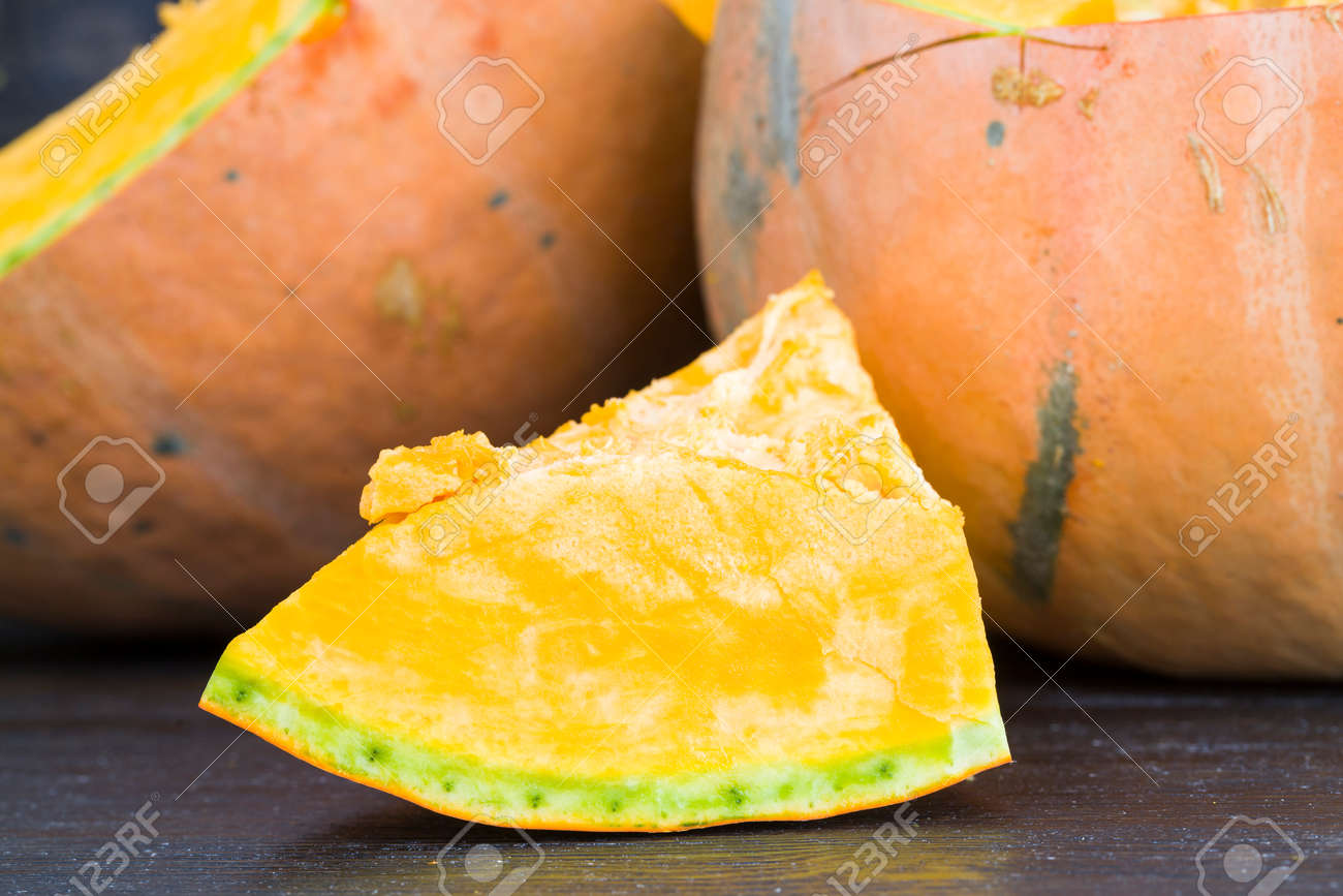 cooking orange ripe pumpkin, slicing vegetables into cubes of different sizes for cooking porridge - 172179676