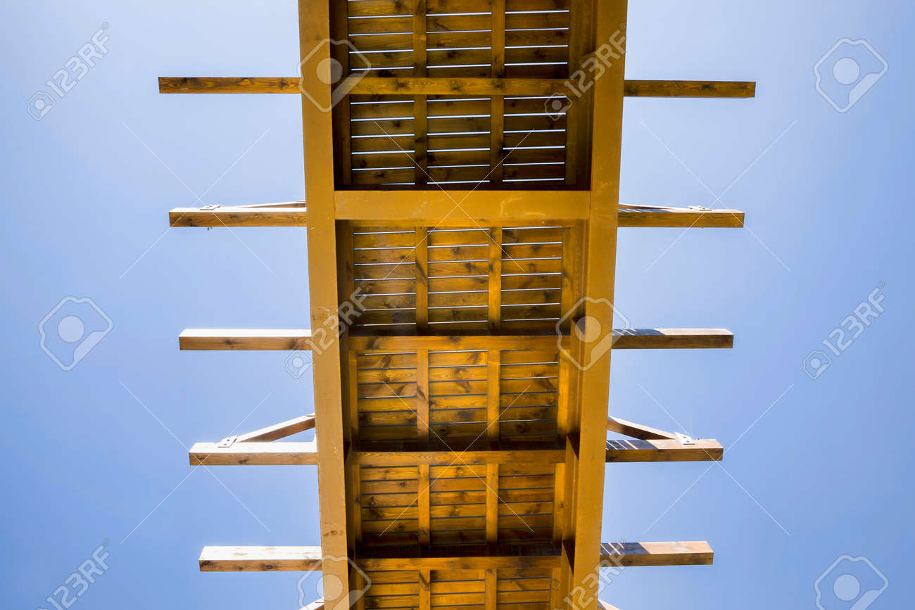 bottom view of a simple wooden bridge over a river against a blue sky in sunny weather - 172179678