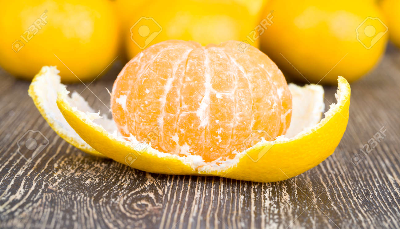 peeled orange juicy tangerine on a wooden table, close-up of ripe sour healthy citrus, winter fruits - 172179682