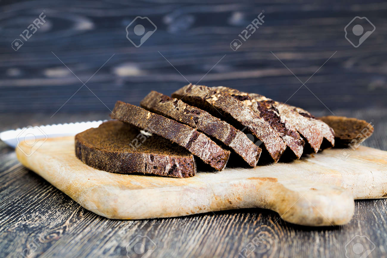 baked dark-colored rye flour loaf of bread, cut into pieces during table setting - 172179683