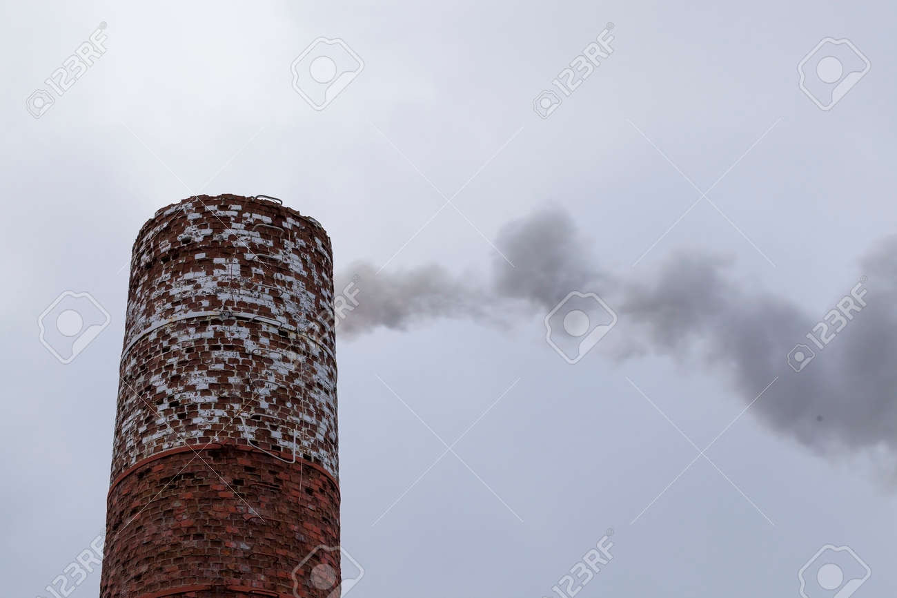 industrial brick pipe from which comes the dark smoke from burning fuel, twilight - 172179689