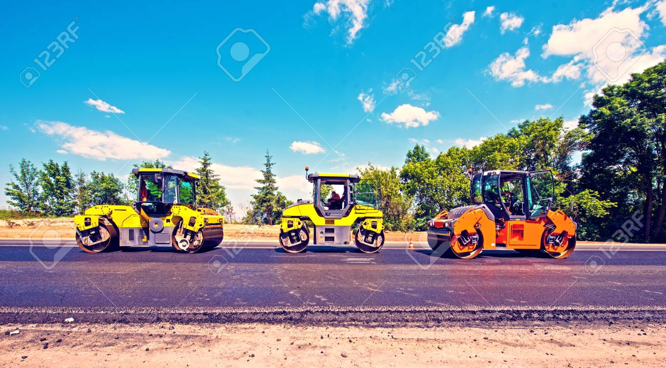 industrial landscape with rollers that rolls a new asphalt in the roadway. Repair, complicated transport movement. - 121405668
