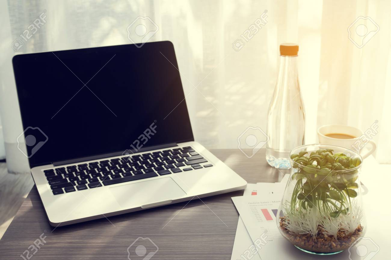 Table de bureau avec écran blanc sur ordinateur portable, bouteille d\'eau,  plante de jardin en pot de verre et rapport statistique au salon, concept  ...