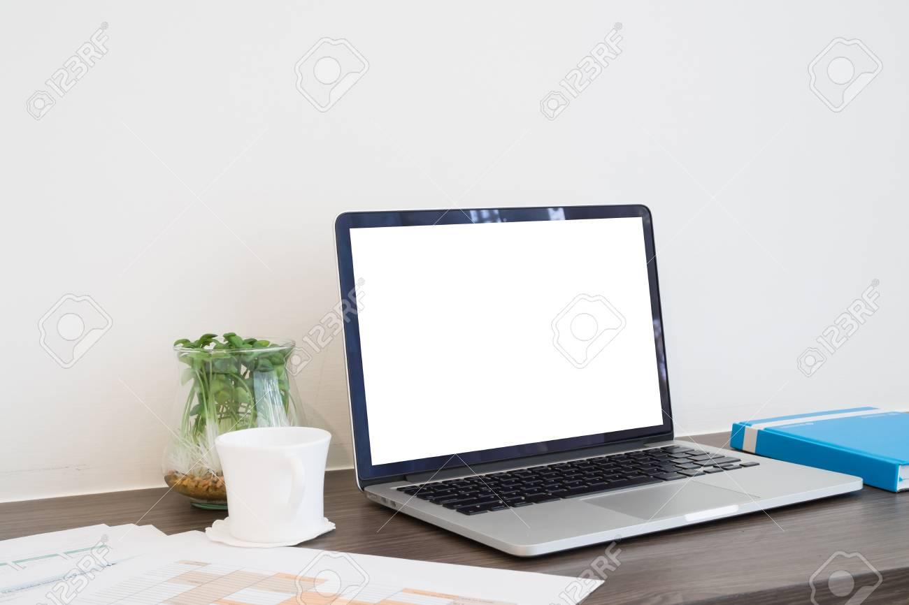 Table de bureau avec écran blanc sur ordinateur portable, tasse de café,  papier de rapport d\'affaires et arbre de jardin sur vase en verre. Voir la  ...