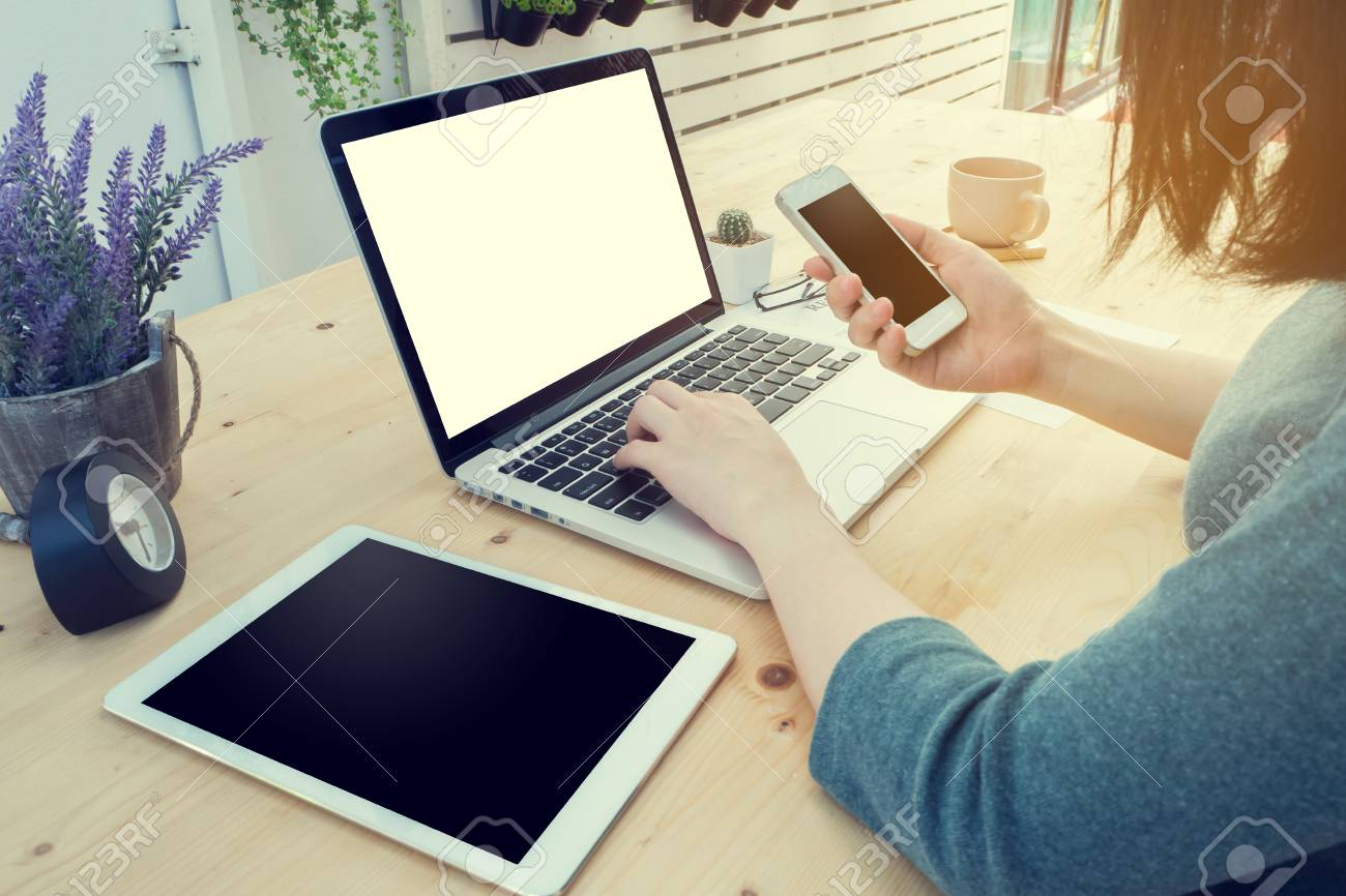 office table with young working woman is hand hold smartphone,