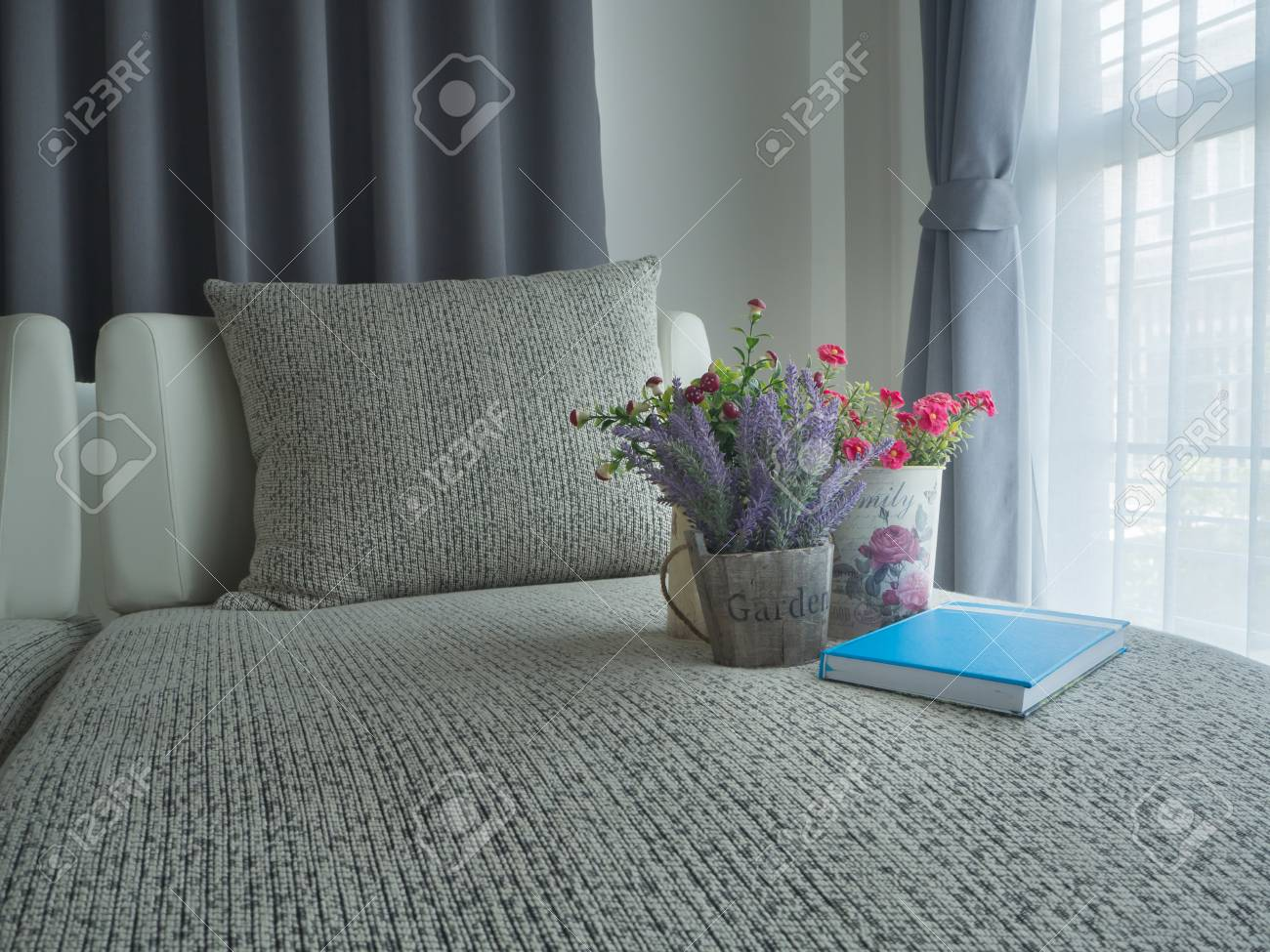 modern vintage sofa with variety colorful flower on pot and notebook..