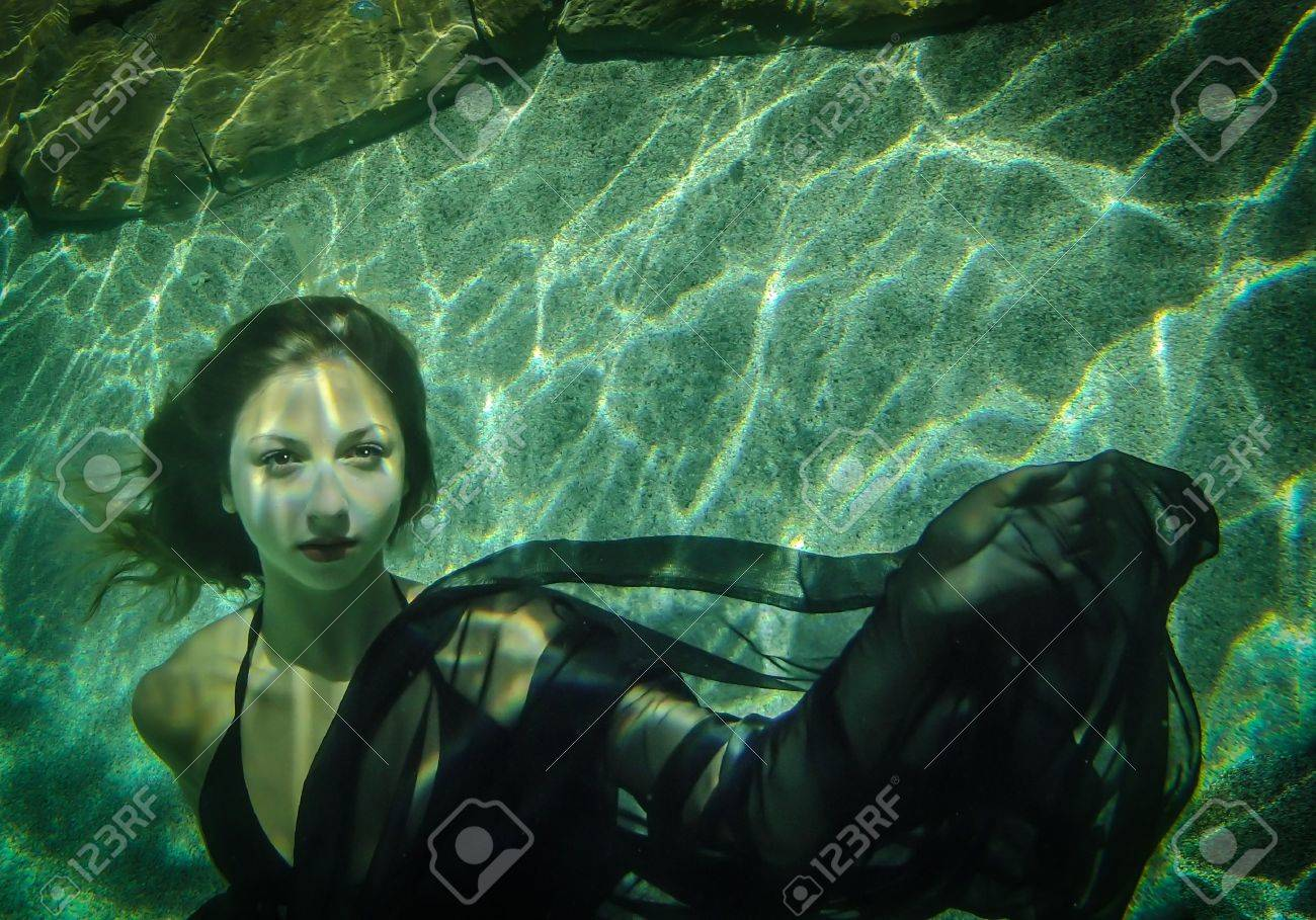 Beautiful young woman floating underwater in a black dress Stock Photo - 15041640