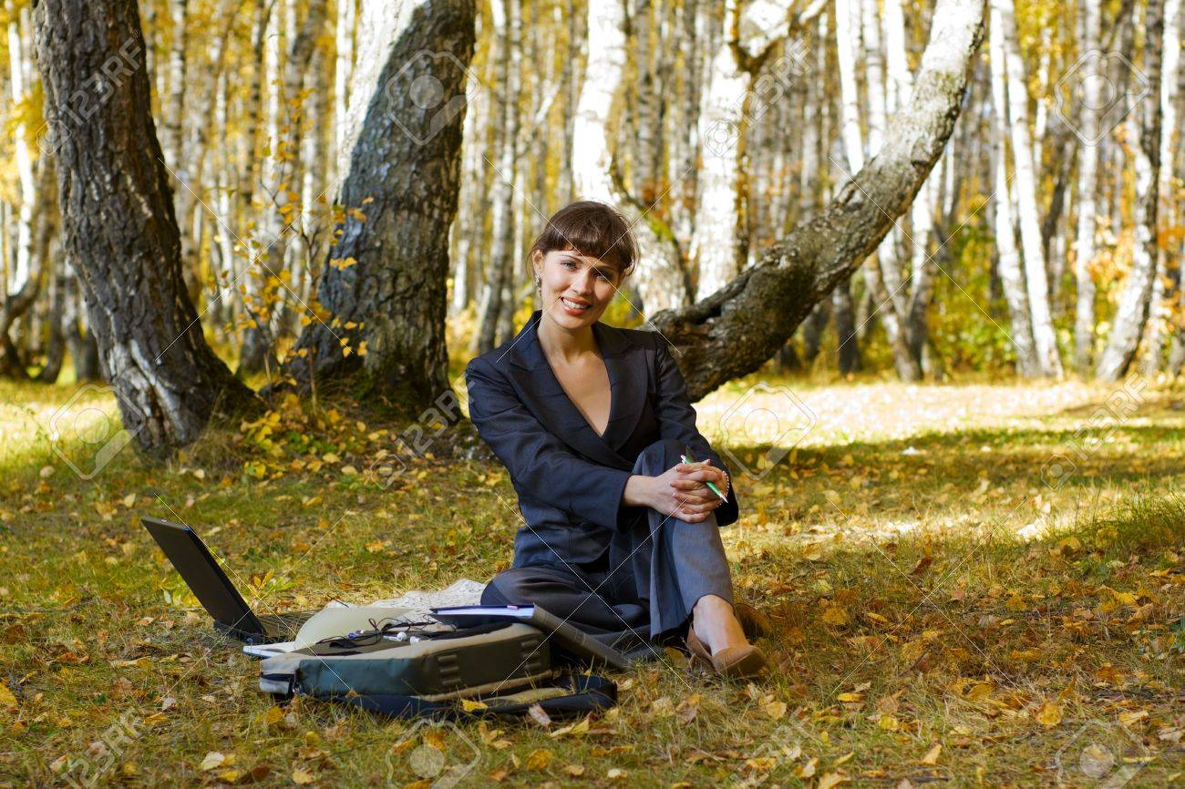 Young businesswoman using laptop in the birch forest. Stock Photo - 5745183
