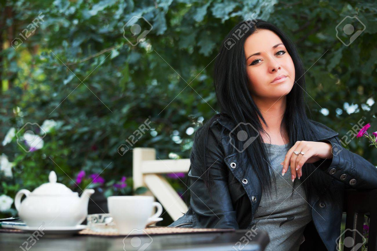 Young woman drinking tea at sidewalk cafe Stock Photo - 9835555