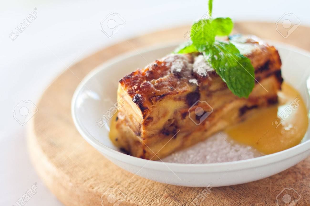 Baked Bread Pudding With Raisins Baked In Creamy Egg Custard Served With Warm Vanilla Sauce And