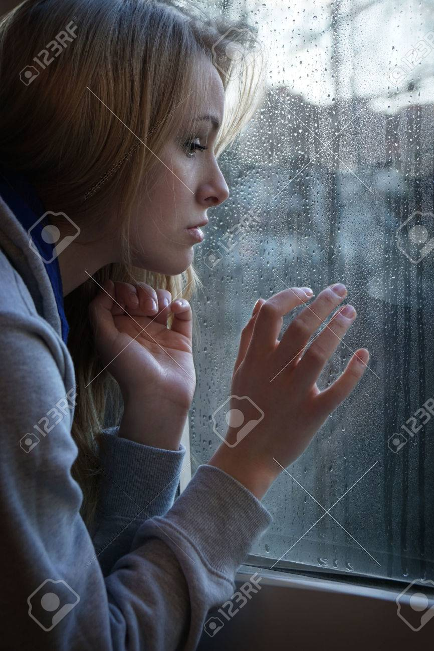 sad young woman looking through window with raindrops - 37236933