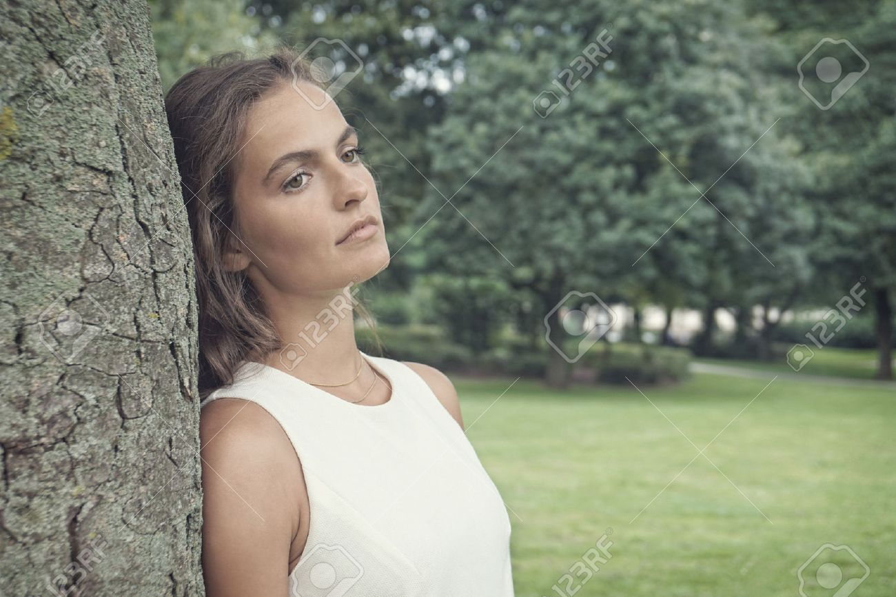 Sad Young Woman Leaning Against Tree With Vintage Faded Filter Effect Stock Photo
