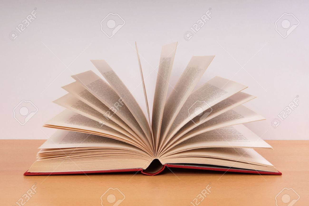 open hardcover book with turning pages in fan shape on desk stock photo 47181675 - Book Pages