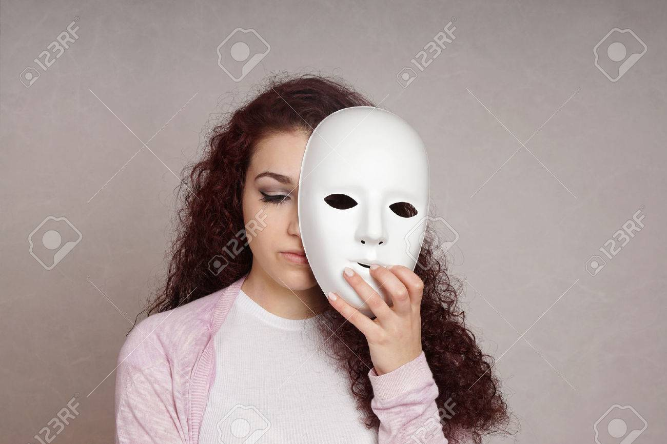 sad depressed young woman hiding her face behind mask - 52083349