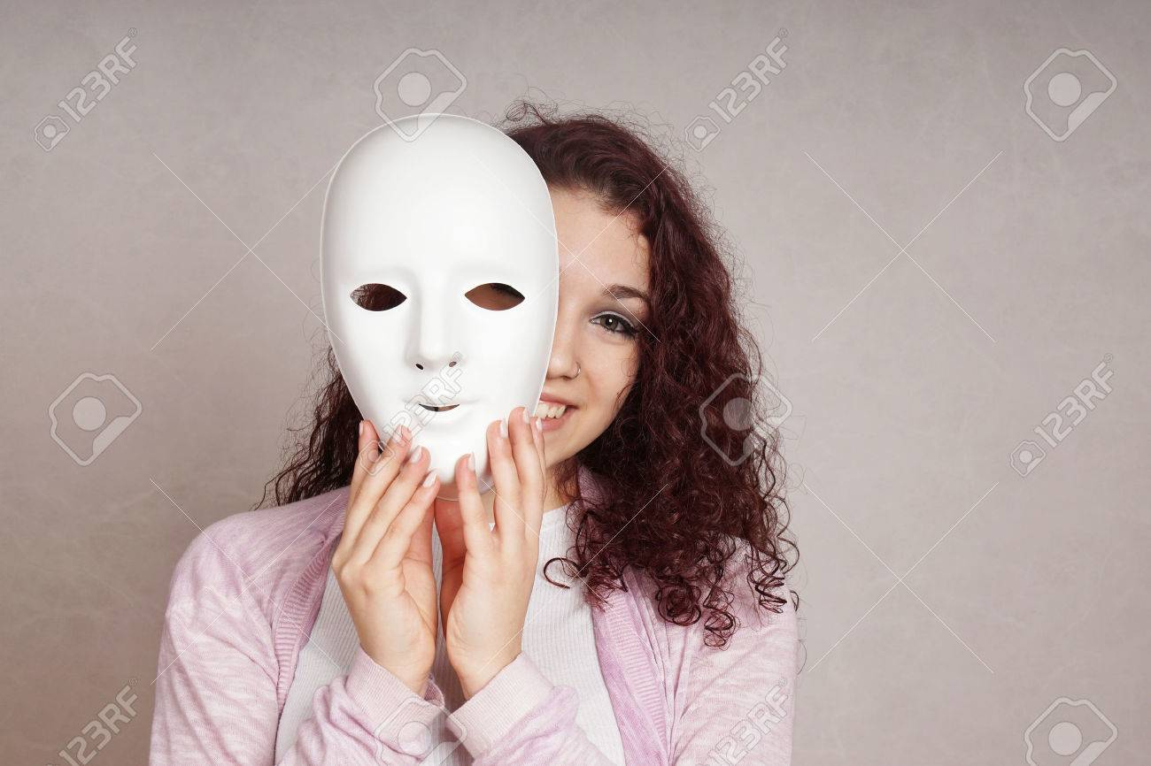 smiling young woman peeking from behind mask - 52083353