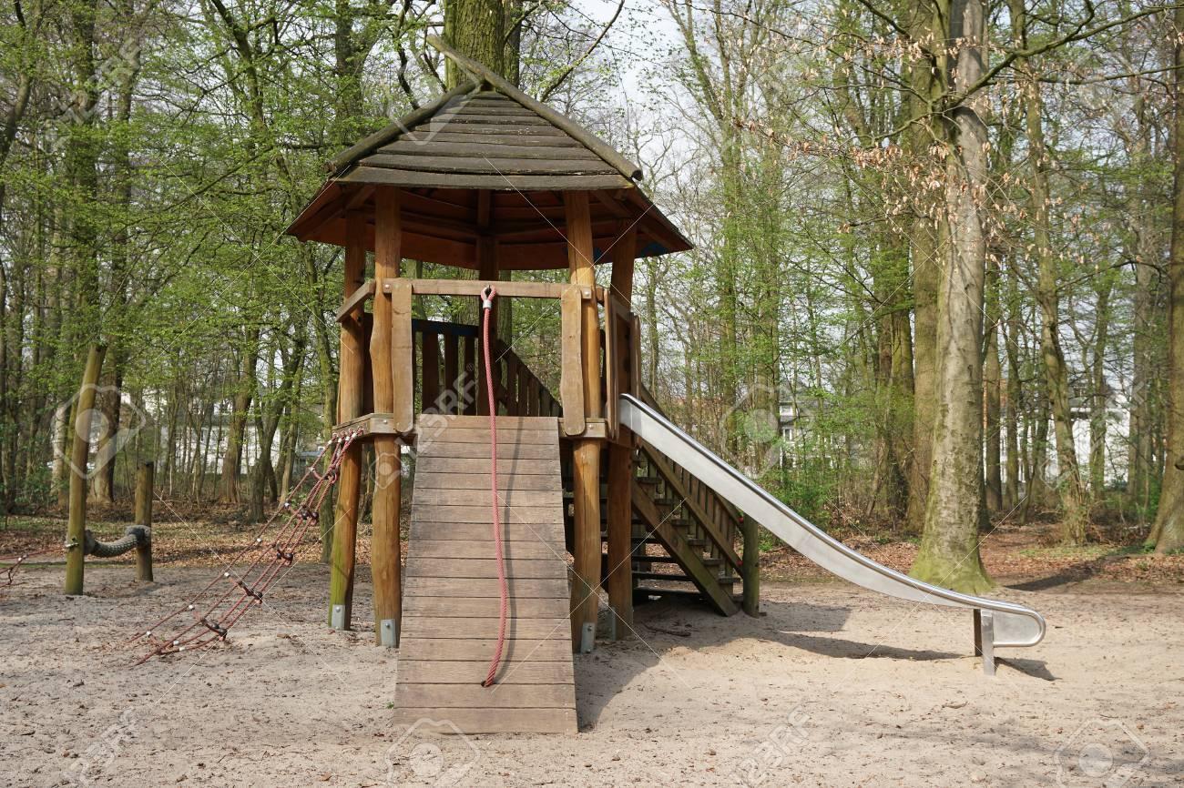 Klettergerüst English : Spielplatz im wald mit holzhütte klettergerüst und rutsche