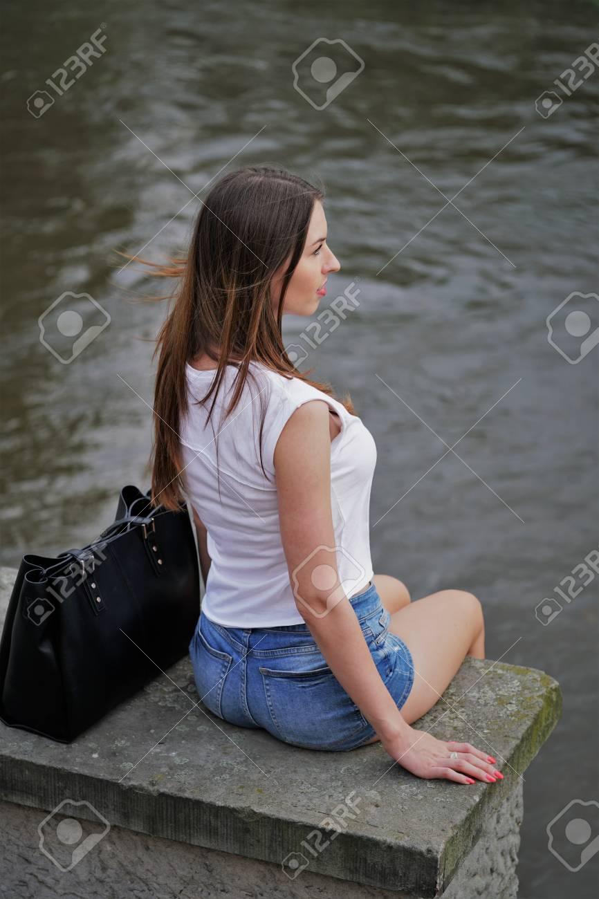 Rückansicht Der Jungen Frau In Hotpants Oder Beute Shorts Sitzen Am ...