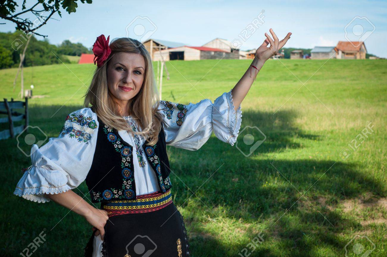 beautiful woman with red flower in her hair posing in Romanian traditional costume Stock Photo - 20896790