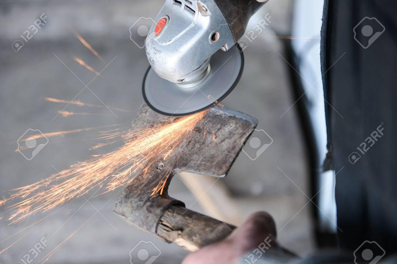 nahaufnahme von einem mann eine axt schärfen mit elektrischen