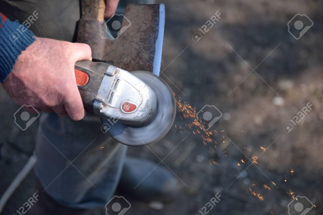 nahaufnahme eines mannes, der eine axt mit elektrischen schleifer