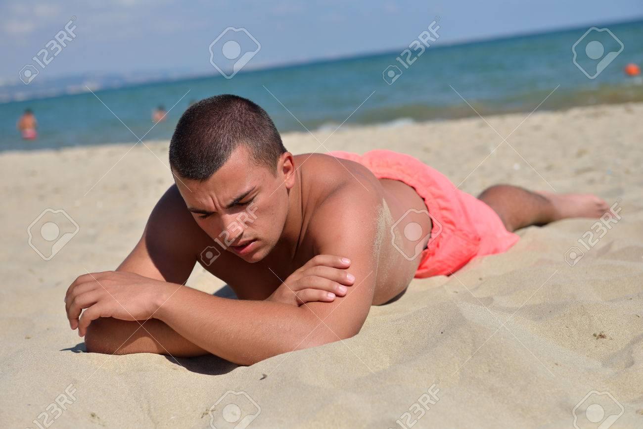 Junger Mann Auf Dem Sand In Der Sonne Liegen Zu Bräunen Beim