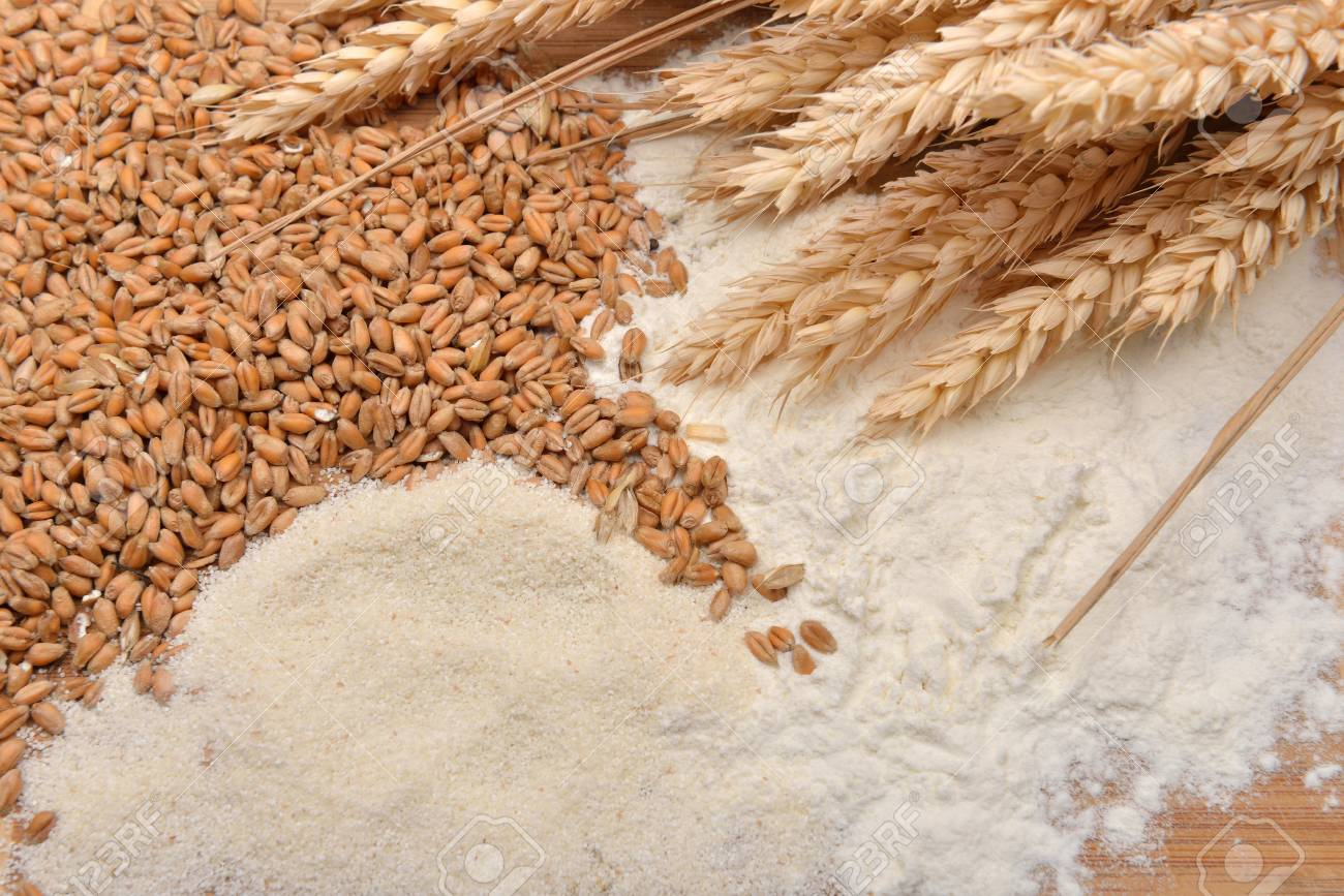Grains, Wheat Ears And Flour On A Wooden Table. Concept Of Making Food From