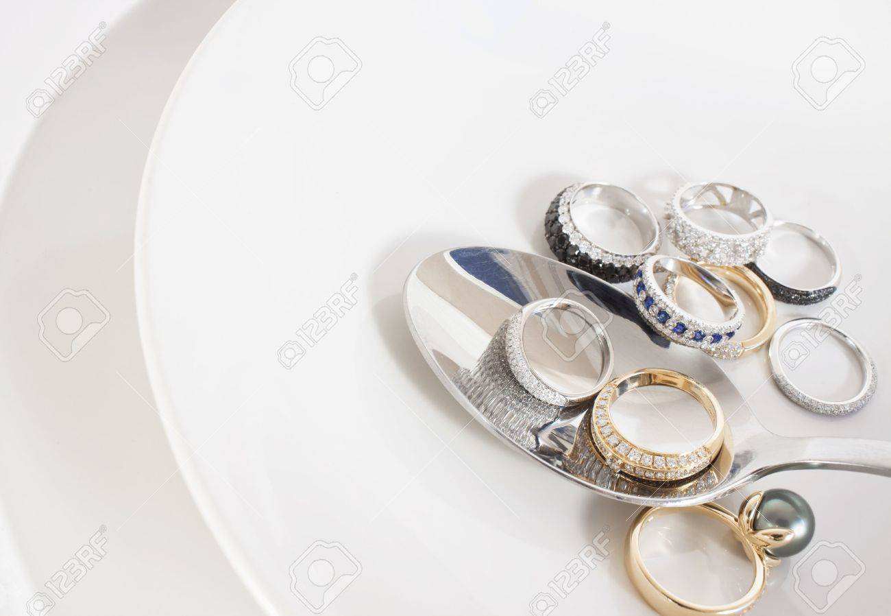 Bunch of transparent and black diamond rings on white soup plate and spoon. White and yellow gold, pearl and sapphires. Stock Photo - 5344221