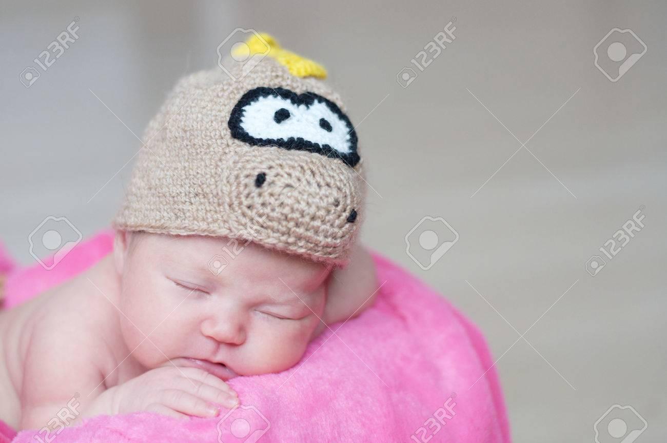 fcd3518a1 Cute Happy Newborn Baby In Dragon Knitted Cap Sleeping In Basket ...