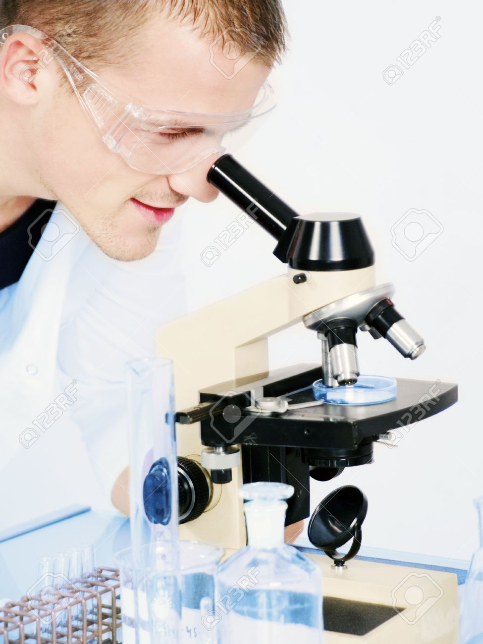 smiling man researching on a microscope stock photo picture and stock photo smiling man researching on a microscope