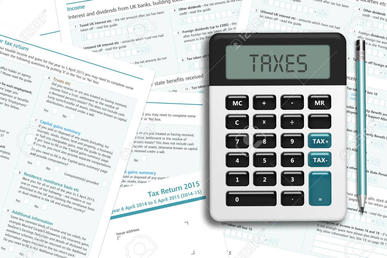 UK tax form with calculator lying on wooden desk with place for text - 51013185