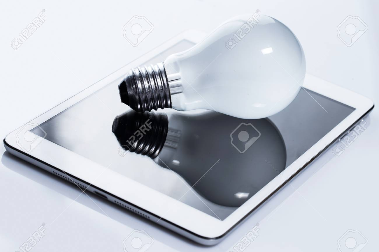 Close up of light bulb and white tablet pc Stock Photo - 24451092