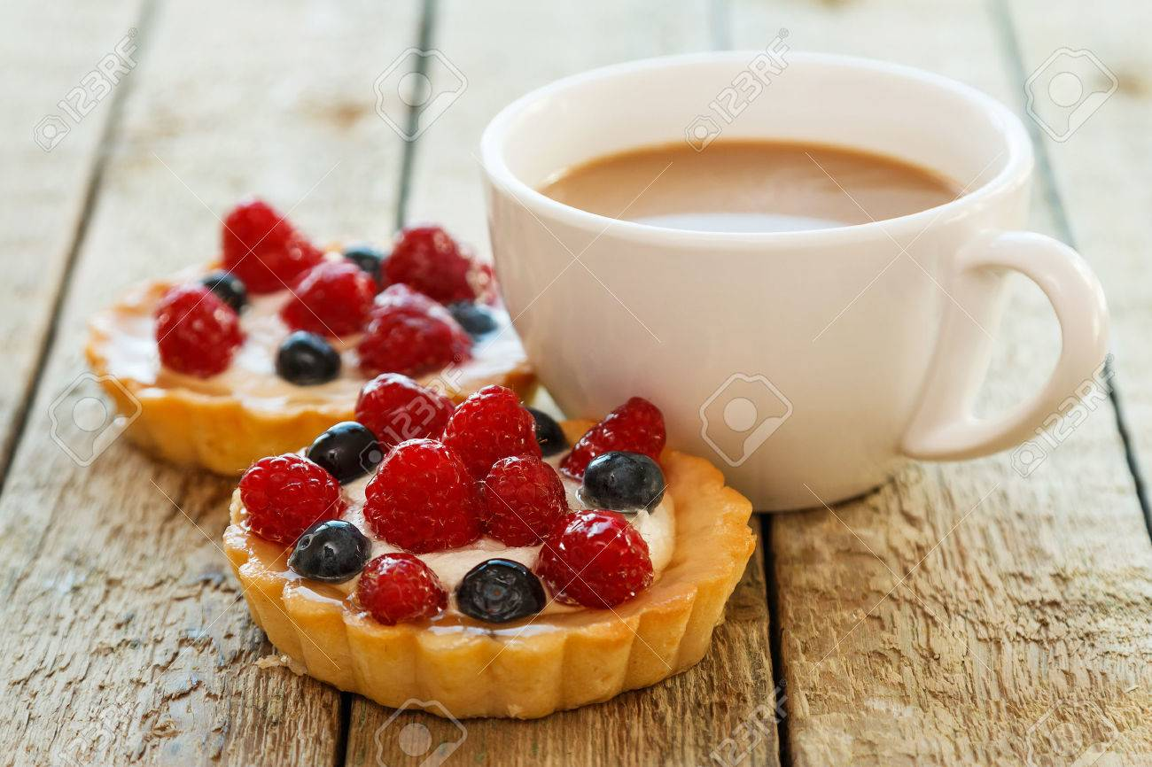 Cup of coffee and sweet cakes with berries on wooden table - 41846694