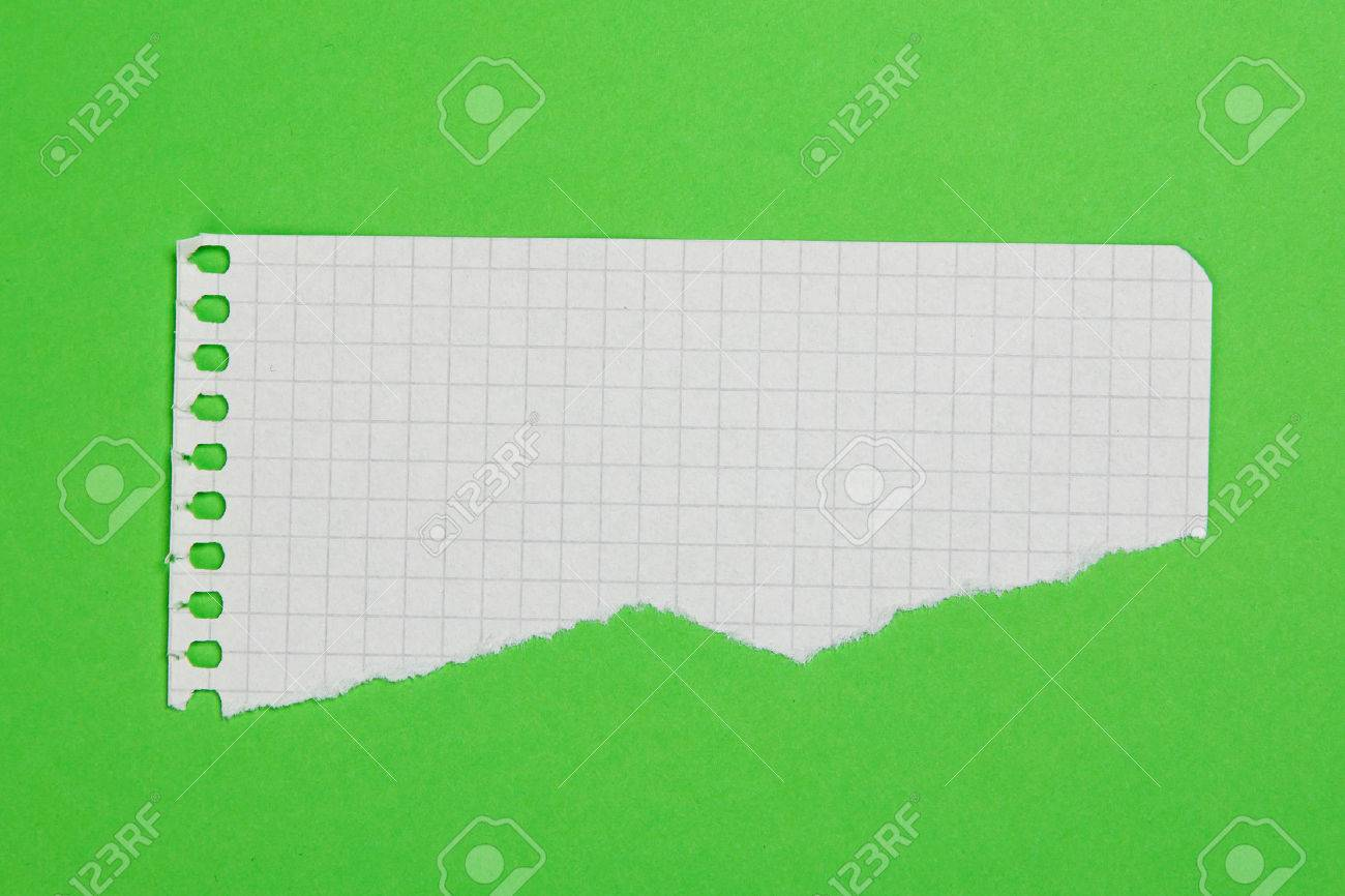 Torn piece of checkered paper on green background - 41840036