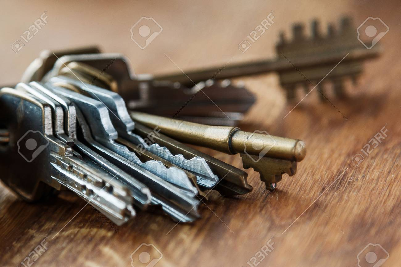 Bunch of different keys on wooden table - 41839888