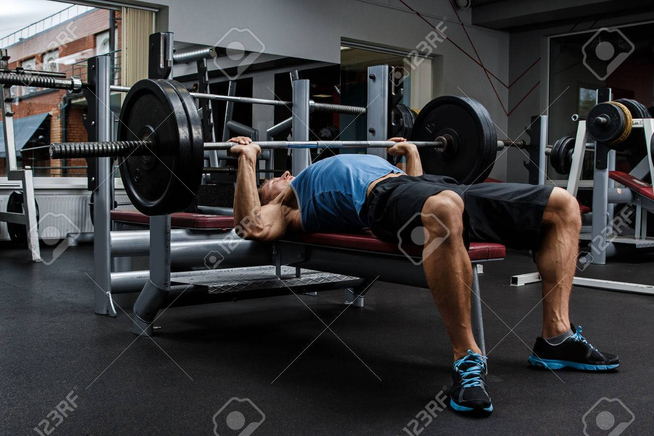 Man during bench press exercise in gym - 56692189