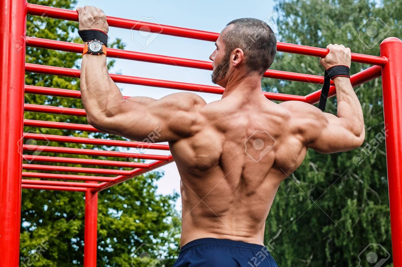 Muscular man doing pull-ups on horizontal bar - 56731780