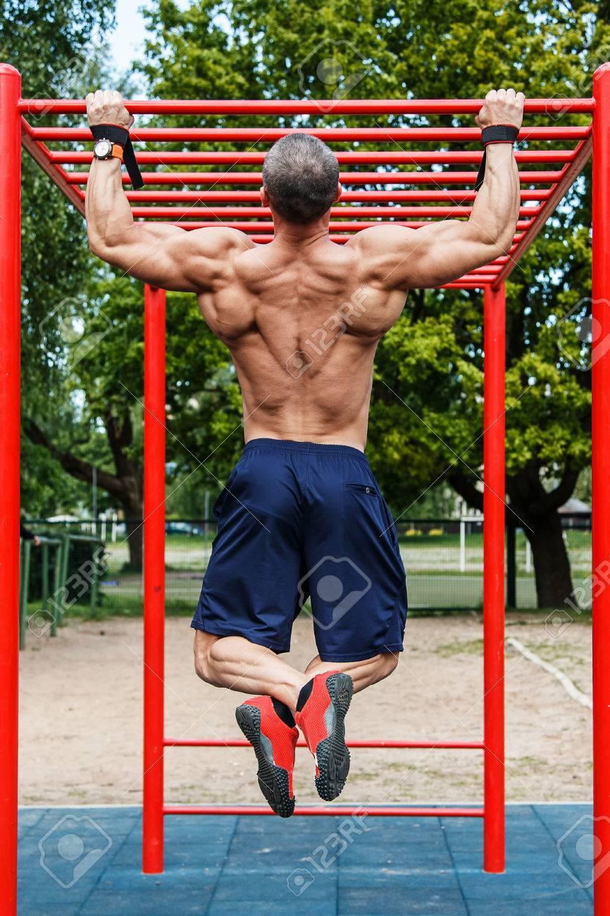 Muscular man doing pull-ups on horizontal bar - 56740410