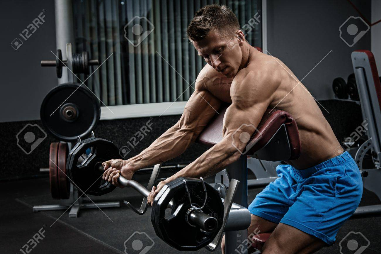 Muscular man training his arms in gym - 56658673