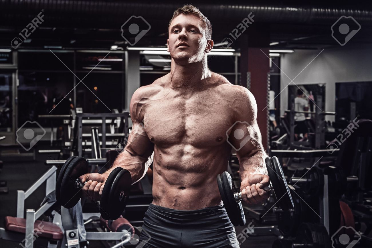 Muscular man with dumbbells in gym - 56658716