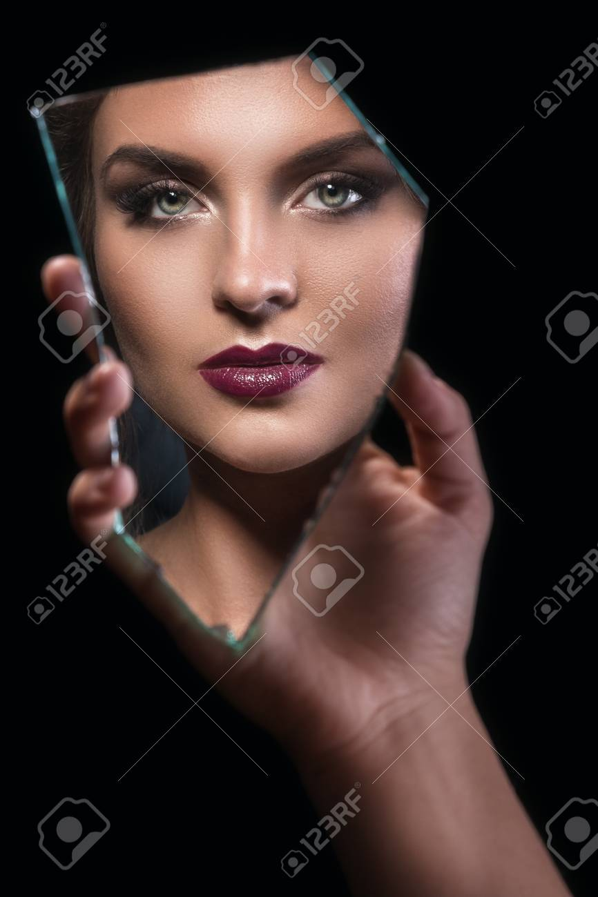 Hand holding a splinter of mirror with female face in reflection - 104232126